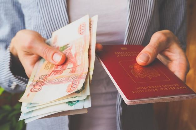 手にロシアのパスポートとメモルーブル。 Premium写真