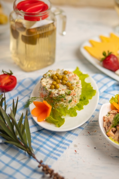 Russian salad olivie, stolichni with boiled vegetables, meat and grean beens Free Photo