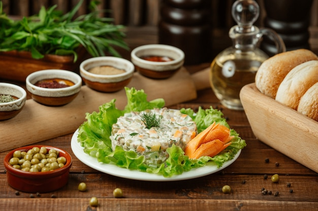 Russian salad stolichni served on green salad leaves and decorative carrot with green beans Free Photo