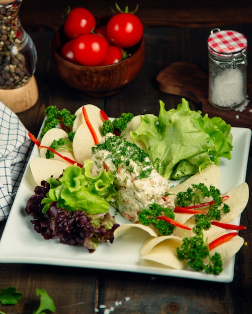 Russian salad topped with herbs Free Photo