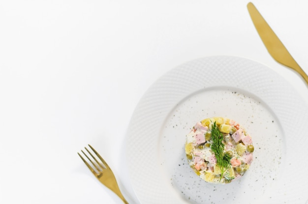 Russian salad on a white plate with a golden knife and fork Premium Photo