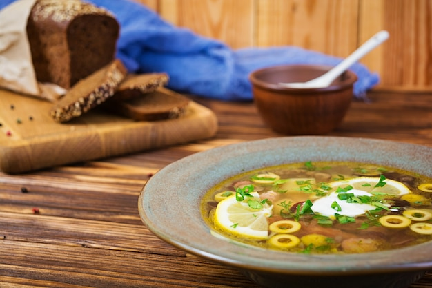 Russian soup solyanka with sour cream on wooden background Premium Photo