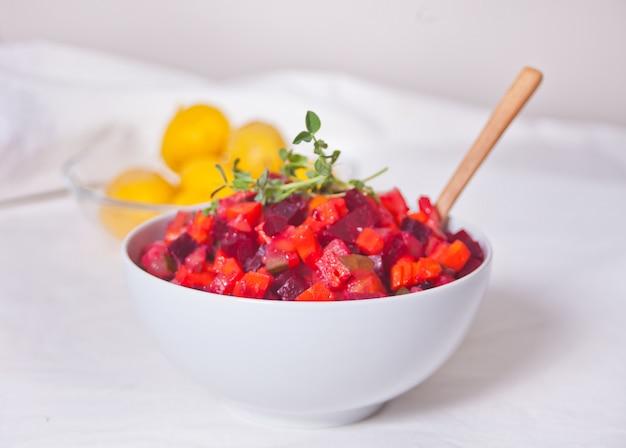 白いボウルにロシアのビネグレットビートのサラダ。 Premium写真