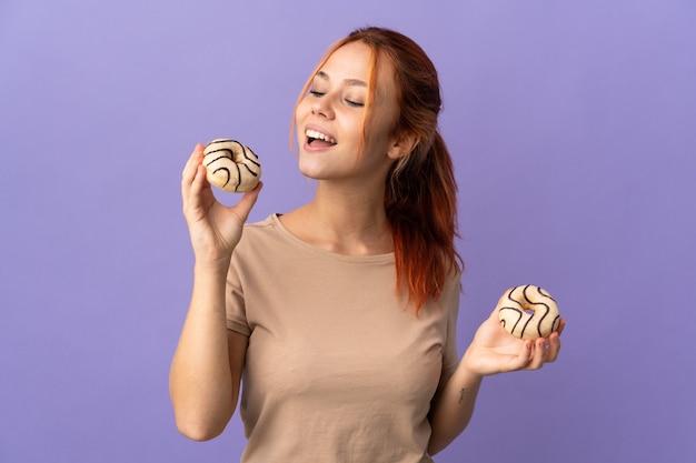 幸せな表情でドーナツを保持している紫色に分離されたロシアの女性 Premium写真
