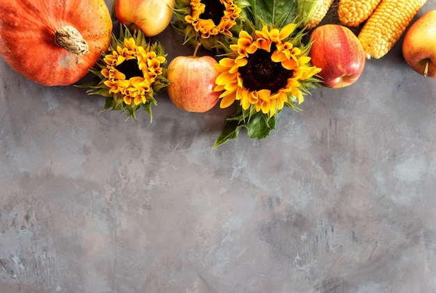A rustic autumn still life with pumpkin, apples and corn cobs Premium Photo