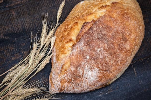 木製のテーブルで素朴なパン。フリーテキストスペースと暗い不機嫌そうなスペース。 無料写真