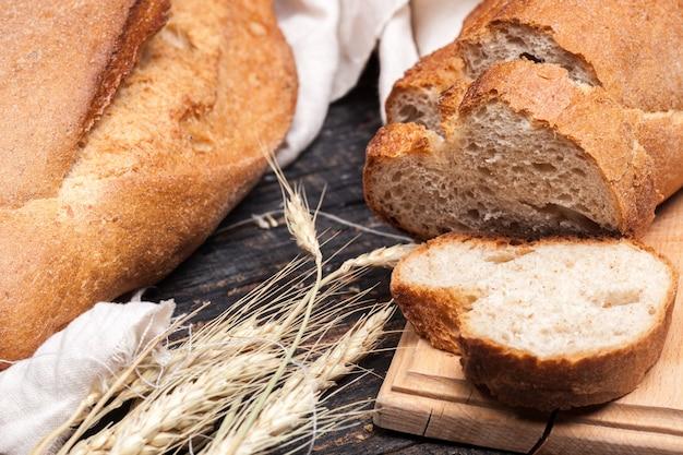 Деревенский хлеб на деревянный стол. темный деревянный Бесплатные Фотографии