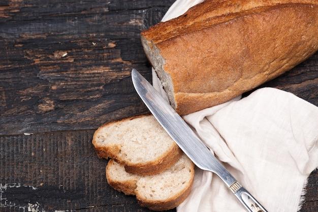 木製のテーブルで素朴なパン。フリーテキストスペースを持つ暗い木質空間。 無料写真