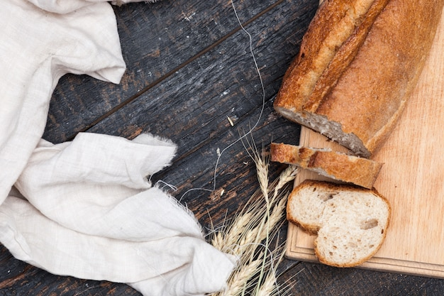 Rustic bread on wood table with wheat and cloth Free Photo