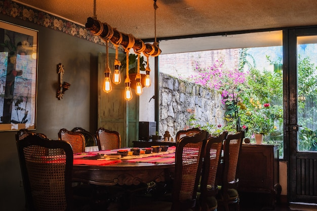 빈티지 주방의 식탁 위에 전구와 로프로 만든 소박한 샹들리에 무료 사진