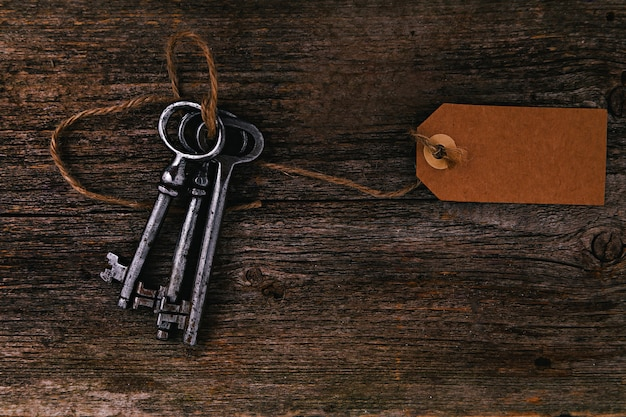 Rustic keys with label on wooden table Free Photo