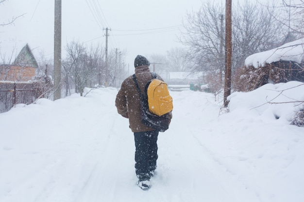 A rustic man is walking down the street in winter with a yellow backpack. snow blizzard Premium Photo
