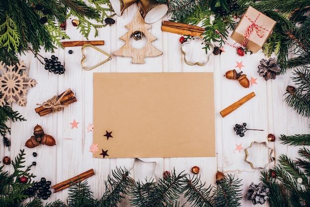 소박한 종이 전나무 나뭇 가지와 소박한 크리스마스 장식으로 만든 원의 중심에있다 프리미엄 사진