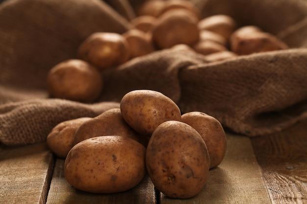 Rustic unpeeled potatoes on a desks Free Photo