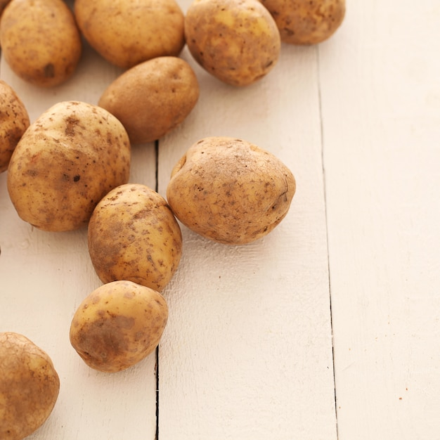 Rustic unpeeled potatoes on a table Free Photo