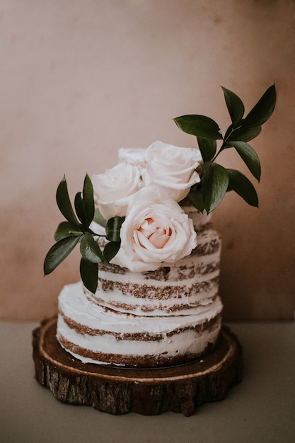 Rustic wedding cake with three white roses topper on brown texture background Free Photo