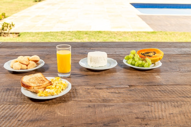 Rustiica wooden table, with breakfast. white dishes with toast and eggs, glass of orange juice, fresh cheese and papaya, and green grapes. Premium Photo
