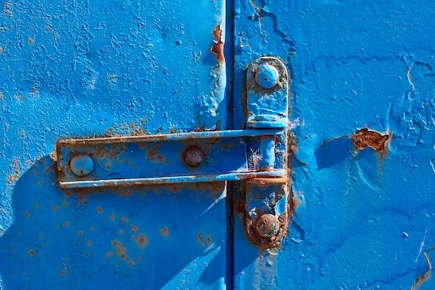 Rusty hinge on old blue rusty metal door, closeup Premium Photo
