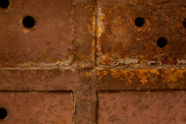 Rusty metal surface with solder and holes Free Photo