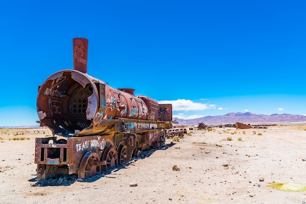 ボリビアのウユニ塩原にある有名な列車の墓場のさびた列車。 Premium写真