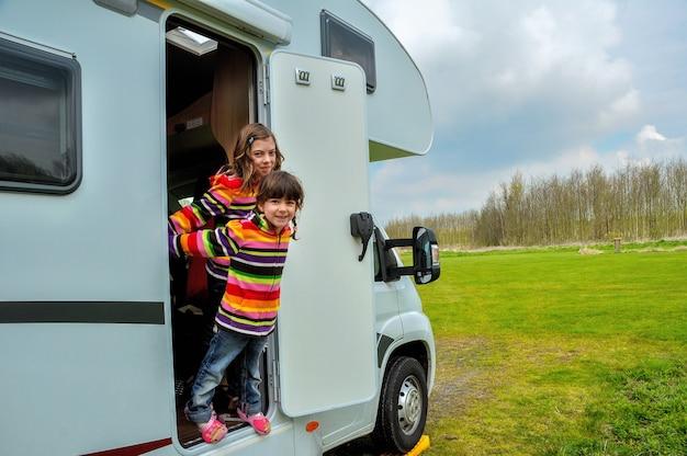 キャンピングカーrvの近くの幸せな子供たち、キャンピングカーで家族での休暇旅行を楽しんで Premium写真