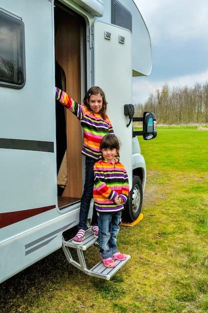 Счастливые дети возле автофургона rv весело проводят время, семейный отдых в дом на колесах Premium Фотографии