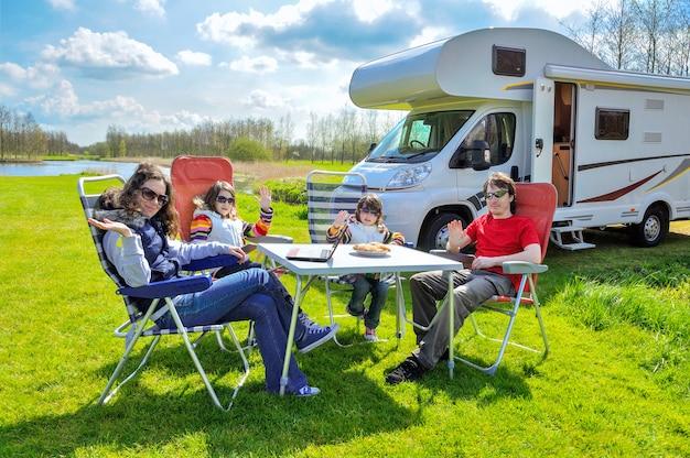 家族での休暇、rv(キャンピングカー)は子供と一緒に旅行、子供たちと幸せな親はキャンプのテーブルに座る Premium写真