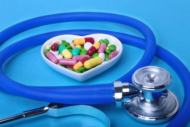 聴診器、rx処方、プレート上のカラフルな品揃えの錠剤とカプセル。 Premium写真