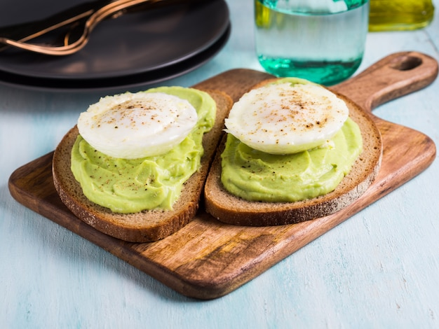 Rye bread avocado toasts with poached egg on wooden serving board. brunch lunch meal Premium Photo