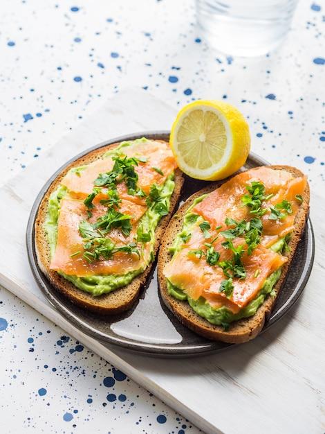 Rye bread avocado toasts with smoked salmon Premium Photo