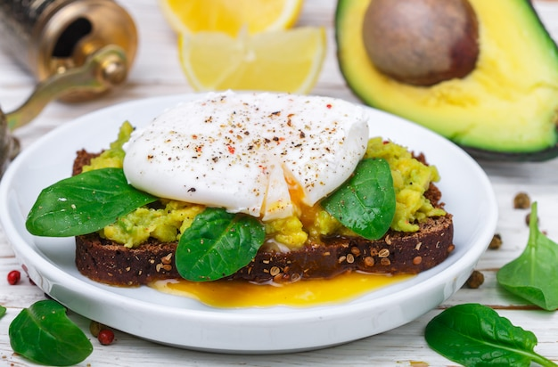 Rye bread toast with coriander, poached egg with green salad spinach Premium Photo