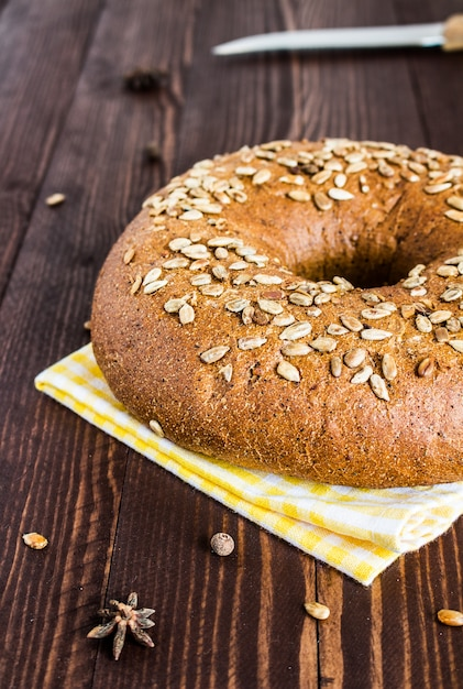 Rye bread with sunflower seeds on towel on wood board Free Photo