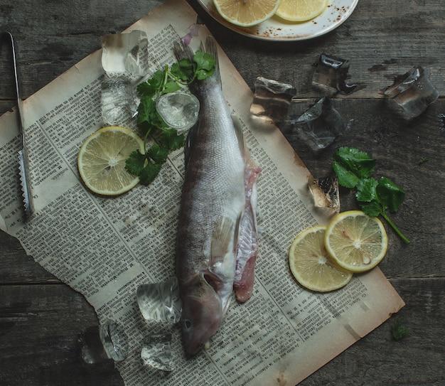 レモンスライスとバジルの紙の上の魚のs製 無料写真