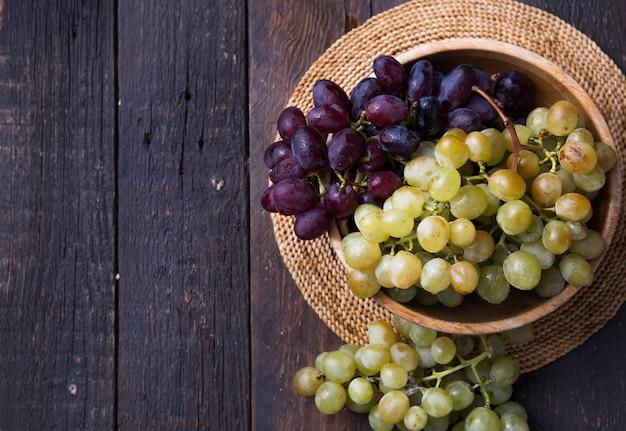木製の表面sの健康的な果物赤と白ワインブドウ Premium写真