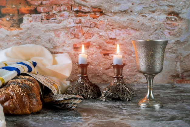 Sabbath jewish holiday challah bread and candelas on wooden table Premium Photo