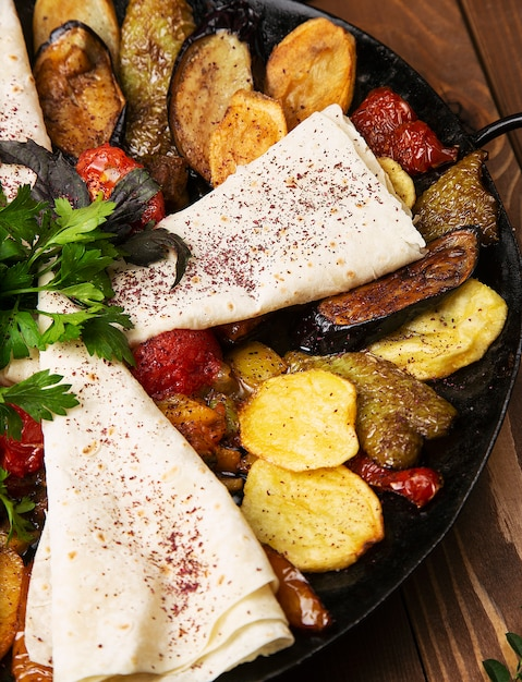 Sac ici, traditional caucasian meal with fried meat and vegetables served with lavash Free Photo