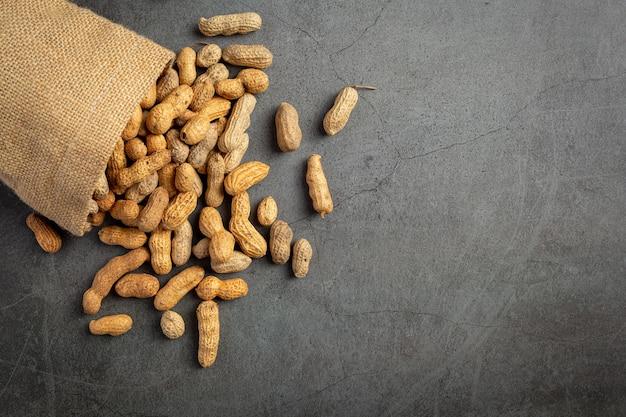 Sacco di arachidi messo su sfondo scuro Foto Gratuite