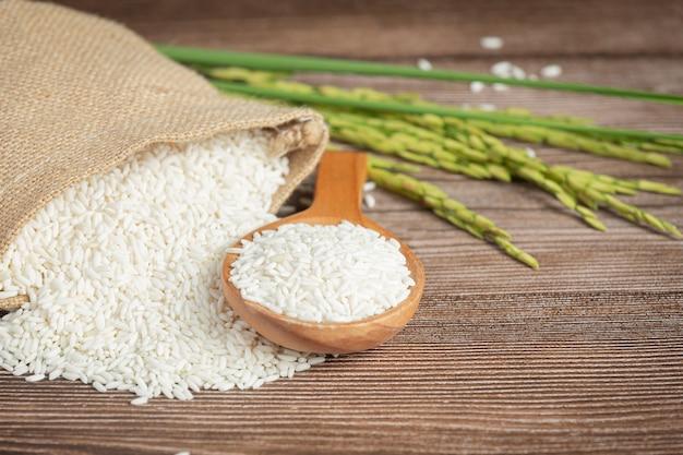 나무로되는 숟가락과 쌀 공장에 쌀과 쌀 자루 무료 사진