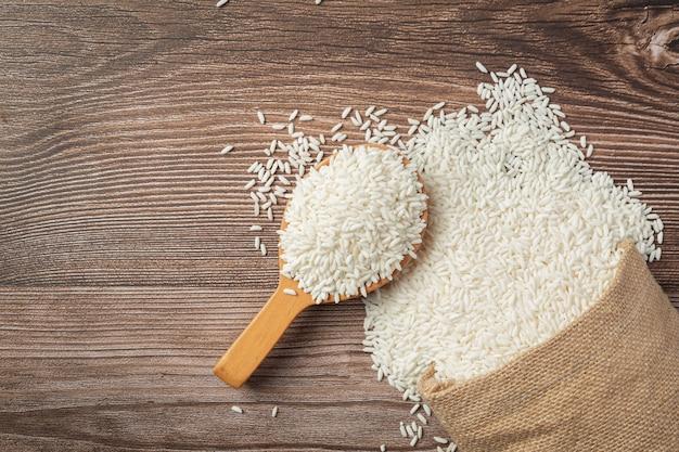 나무 바닥에 흰 쌀과 나무 숟가락 장소 자루 무료 사진