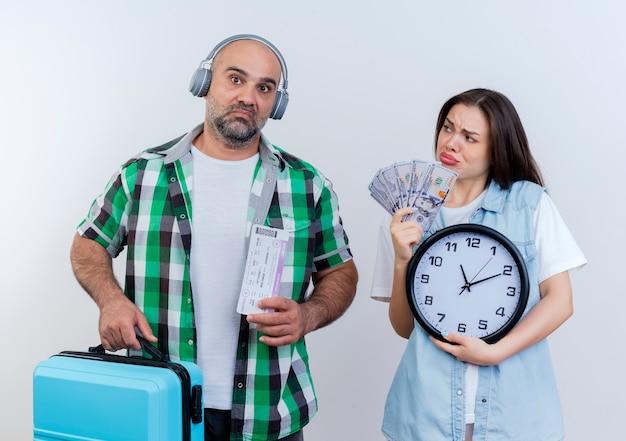 旅行のチケットを持っているヘッドフォンと彼を見ているお金と時計を持っているスーツケースを探している女性を身に着けている悲しい大人の旅行者カップル 無料写真
