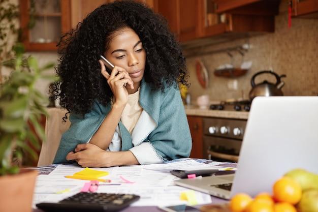 Грустная африканская женщина с афро-прической сидит на кухне перед ноутбуком, разговаривает по мобильному телефону с мужем и говорит ему, что их семью скоро выселят из-за неуплаты за аренду Бесплатные Фотографии