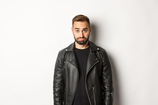 白い背景に立って、カメラをばかげて見て、ふくれっ面の革の黒いジャケットの悲しいとかわいい男。 無料写真