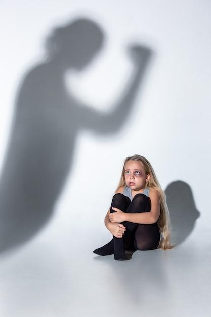 壁の影を怖がって泣いている傷ついた目、血を流した悲しくて怯えた少女。 無料写真