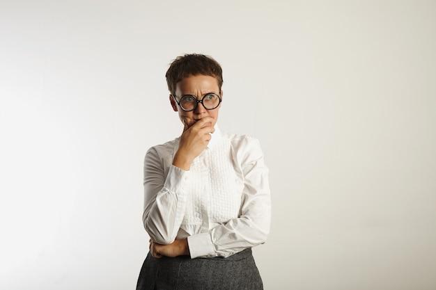 何かを考えている白い古典的なブラウスと灰色のツイードスカートの悲しくて動揺した若い女性 無料写真
