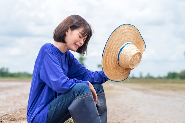 Sad asian farmer woman sitting and cry disappointed to not have water for plant rice at the farm Premium Photo