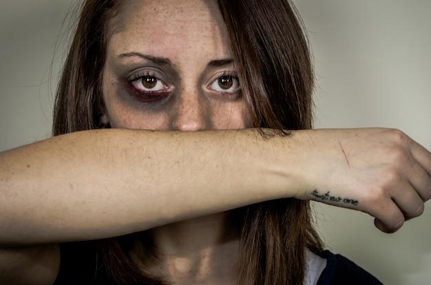 深い表情-白人の人々-女性に対する暴力についての概念で見ている顔に傷を持つ悲しい打たれた少女 Premium写真