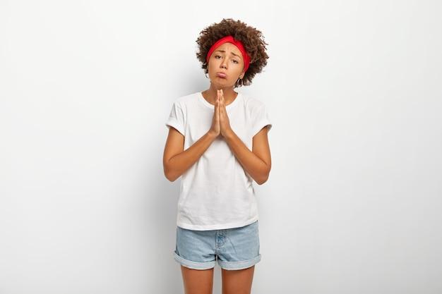 アフロの髪の悲しい物乞いの女性は、祈りのジェスチャーで手を保ち、唇をすぼめ、大きな恩恵を求め、トラブルで手を助け、白い快適なtシャツとジーンズのショートパンツを着て、謝罪する必要があります 無料写真