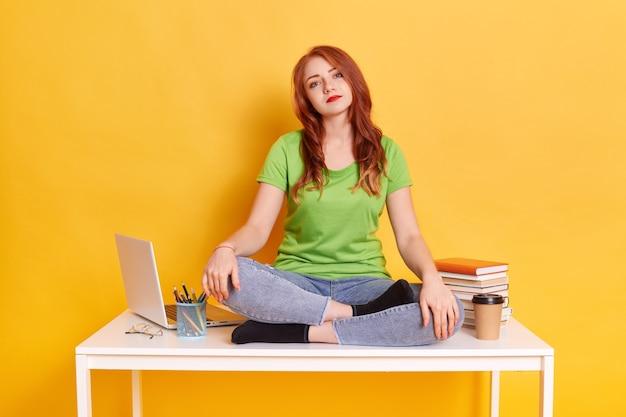 Donna annoiata triste utilizzando laptop seduto seduto sul tavolo con le gambe incrociate Foto Gratuite