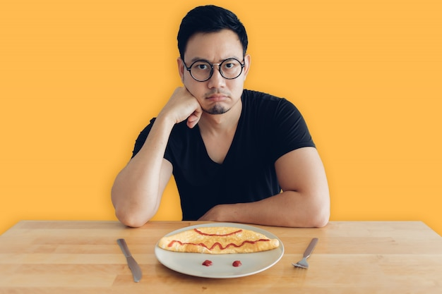Premium Photo | Sad and boring asian man is eating homemade breakfast set  of omelet.