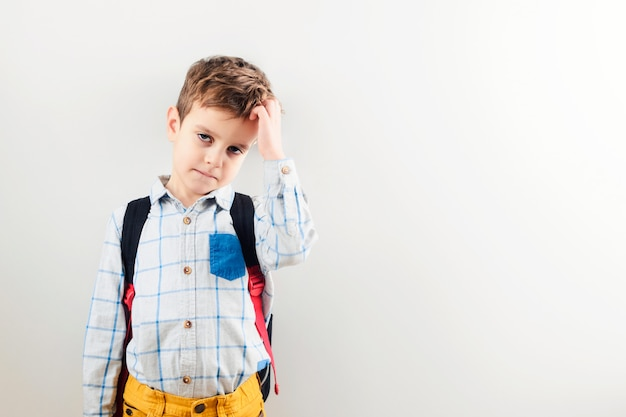 A sad boy with a backpack against a white background. Premium Photo